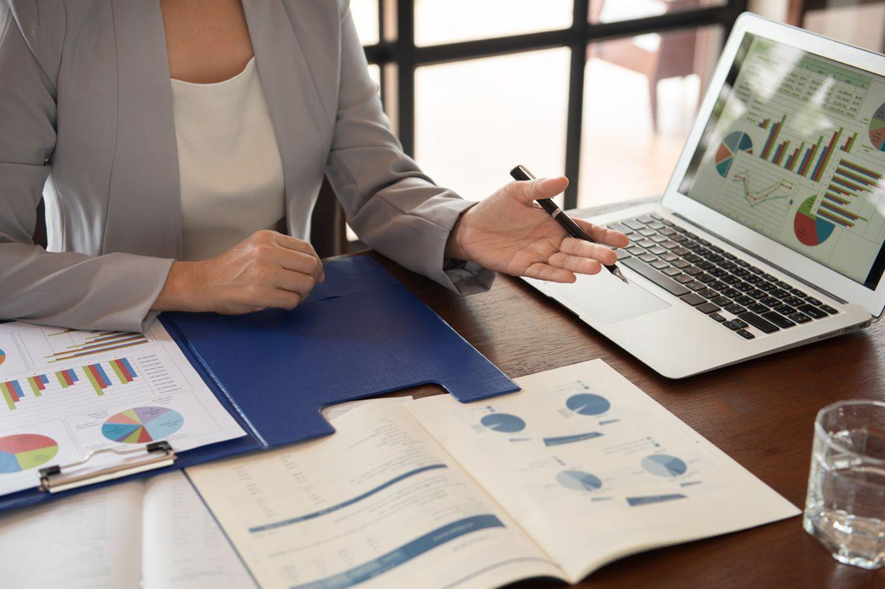 Frau mit Business-Unterlagen und Laptop
