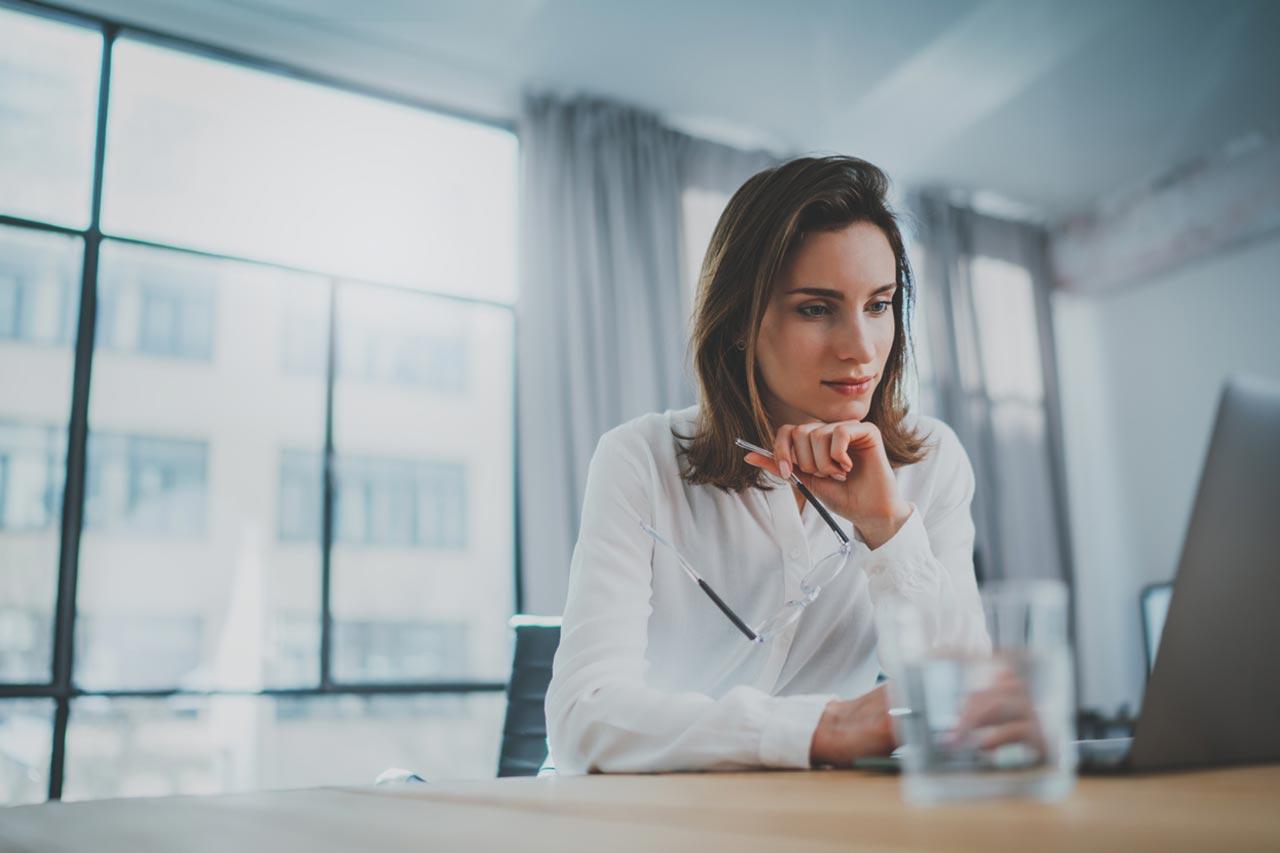 Frau mit Brille in der Hand vor einem Laptop