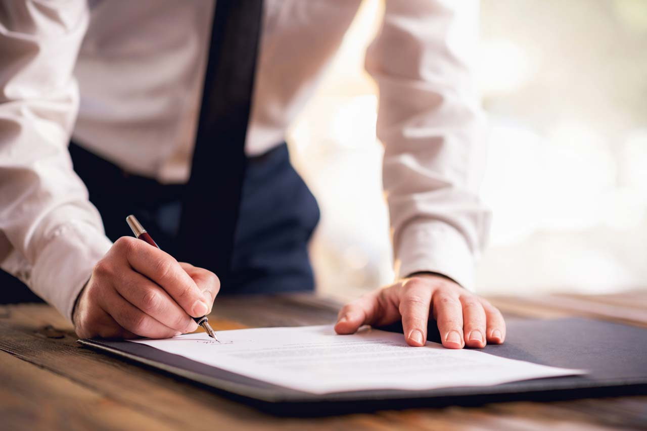 Ein Mann unterzeichnet einen Vertrag mit Füllfeder